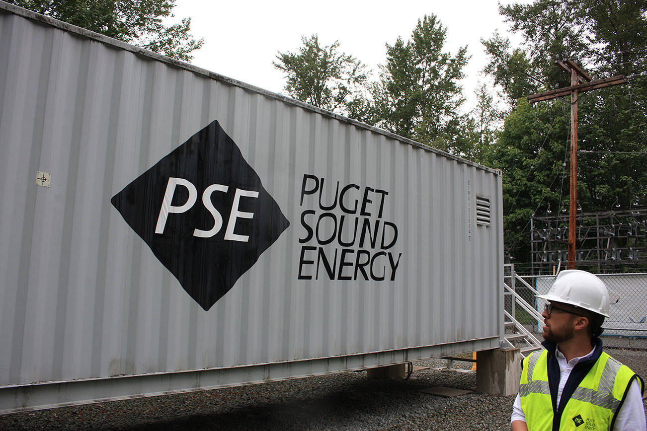 In this 2019 file photo, Puget Sound Energy product development manager John Dooley stands in front of one of four units at the Glacier Battery Storage Project in northwest Washington state. (Sound Publishing file photo)